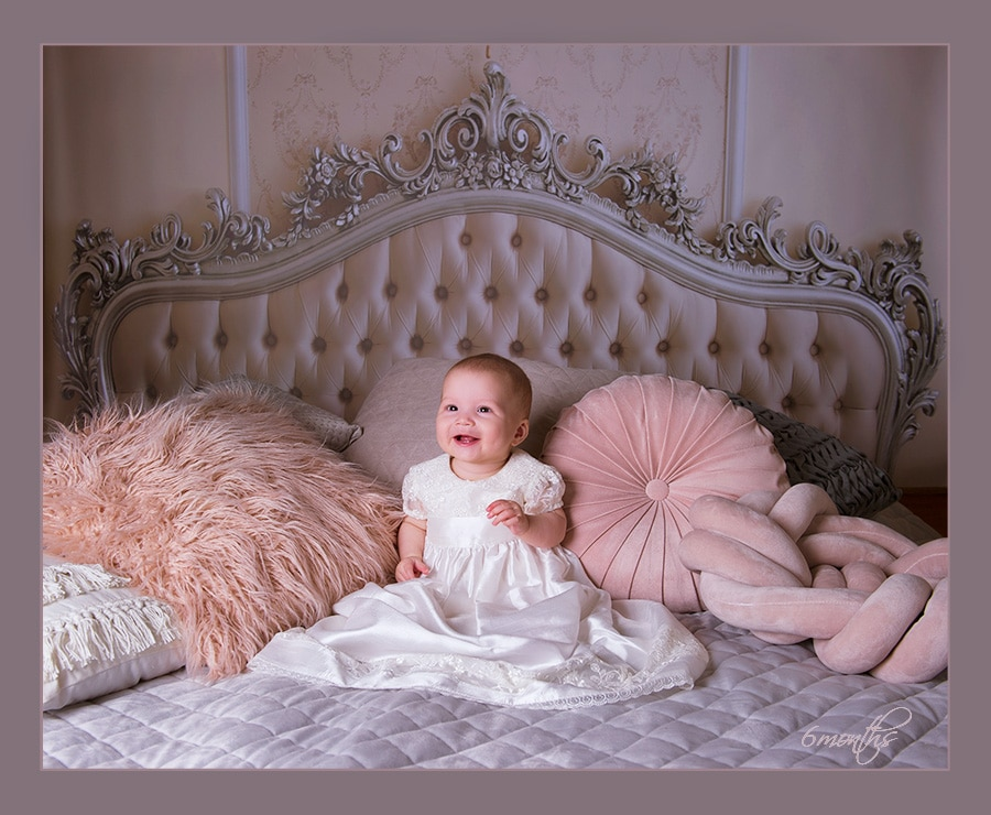 6 month old baby sitting on bed in studio