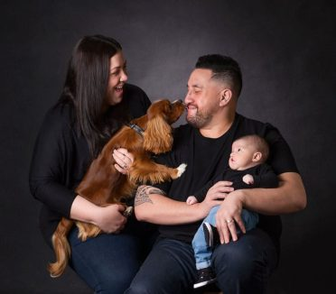 child number one, the family dogs licks dad whilst mum laughs and baby watches, their favourite family portrait