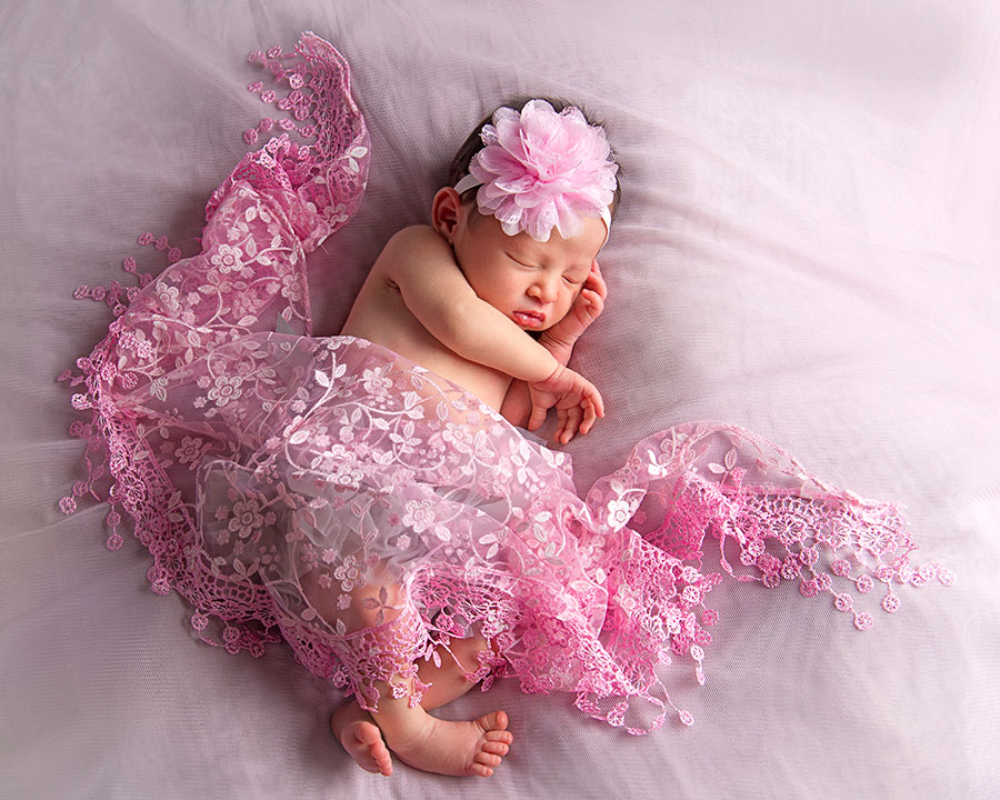 pink newborn props with sleeping baby girl in studio
