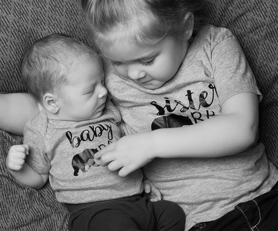 black and white of big sister giving her new brother a cuddle