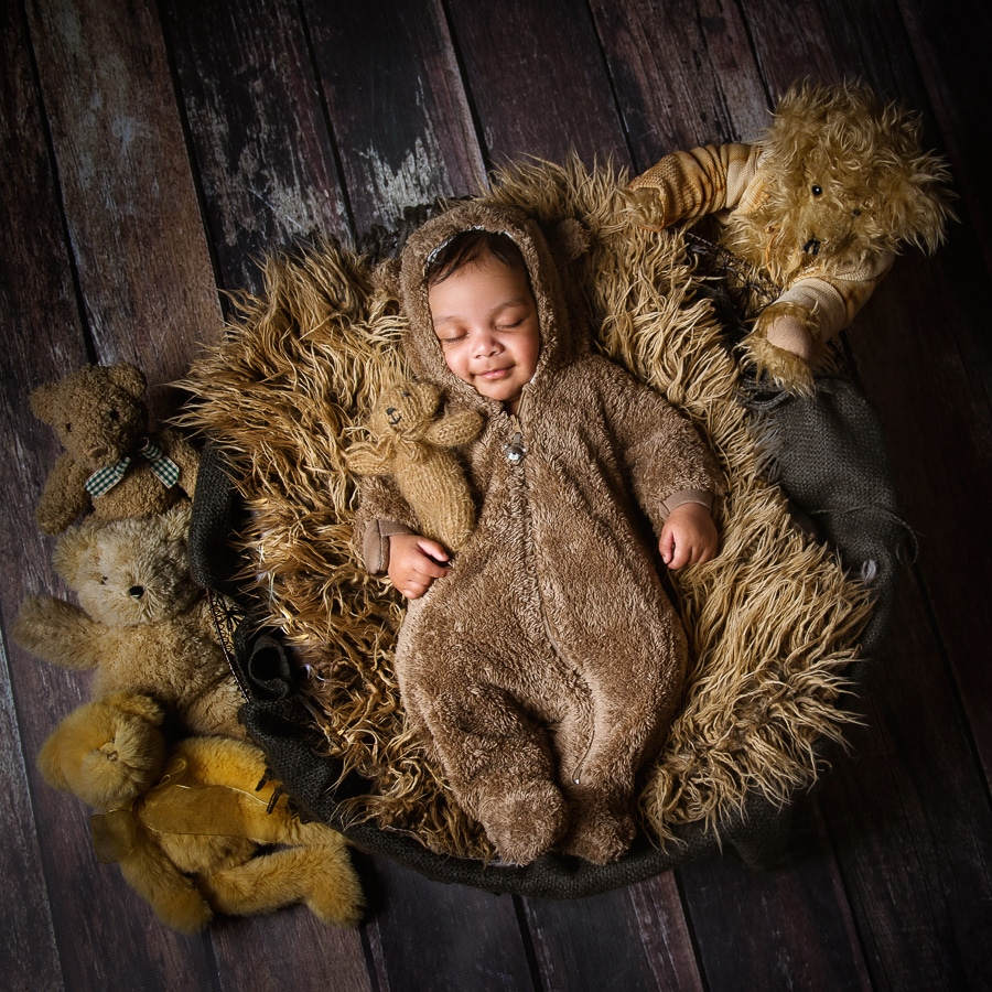 sleeping baby cuddles with bears