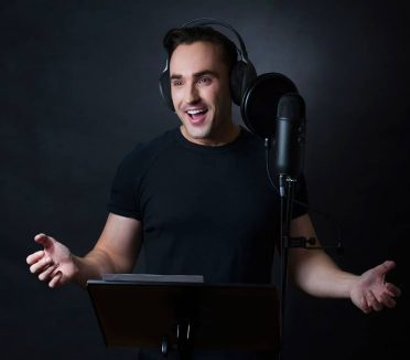 studio folio portrait of young man singing into microphone