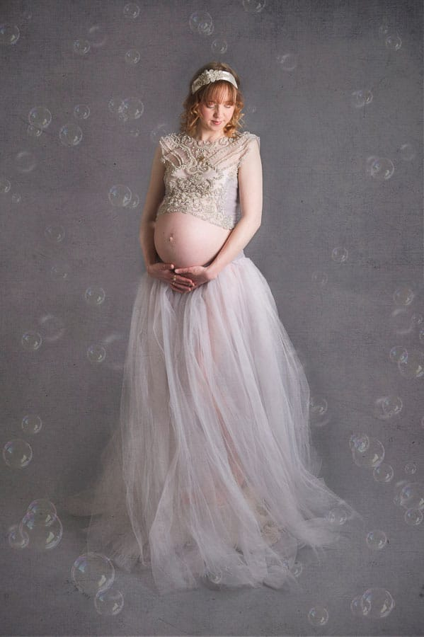 bubbles floating by this beautiful pale skinned pregnant woman wearing a soft grey beaded gown in the studio